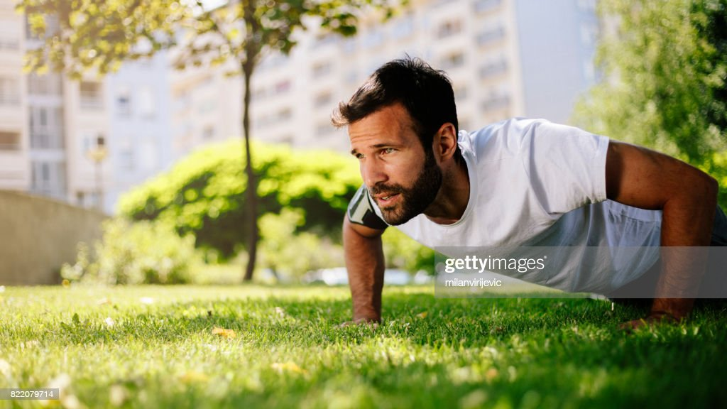 Handsome young man doing pushups in morning training : Stock Photo