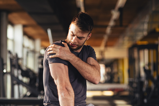 Handsome young man feeling the pain in shoulder at the gym 1057157450