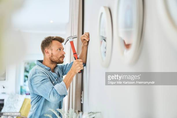handsome young man hammering nail on white wall - hammer stock pictures, royalty-free photos & images