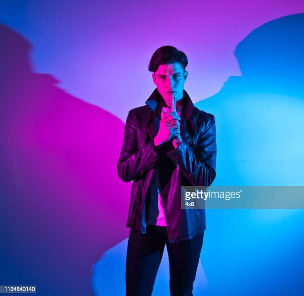 handsome young man in colorful environment - purple pants stock pictures, royalty-free photos & images