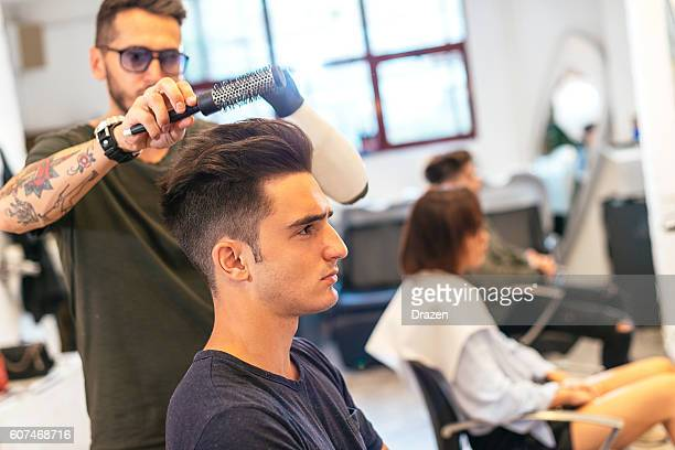 Handsome young man in hair salon having hair cut