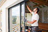 handsome young man installing bay window in a new house construction site