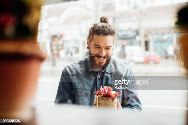 handsome young man looking at flowers - man bun stock pictures, royalty-free photos & images