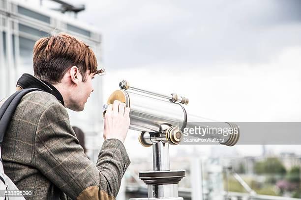 ハンサムな若い男性から見た望遠鏡でパリの街並み