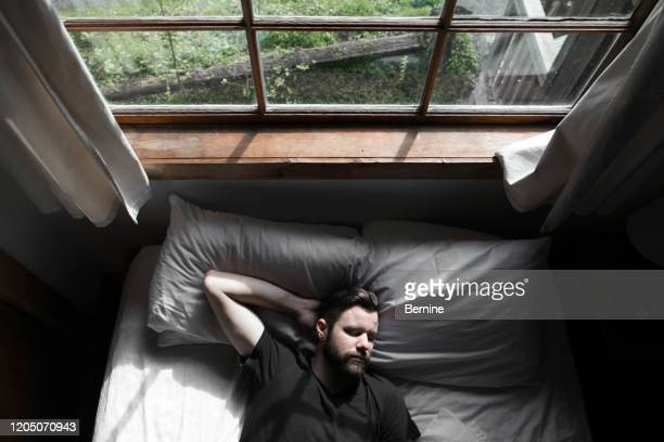 handsome young man on bed smiling - resting stock pictures, royalty-free photos & images