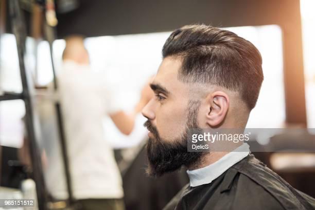 jovem bonito na visita ao cabeleireiro. - barba - fotografias e filmes do acervo