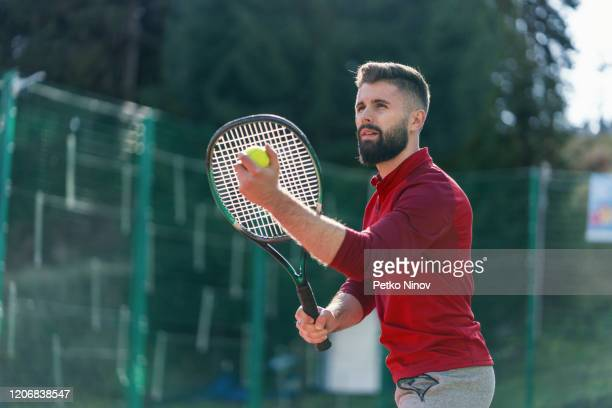 handsome young man playing tennis at the tennis court - tennis player stock pictures, royalty-free photos & images