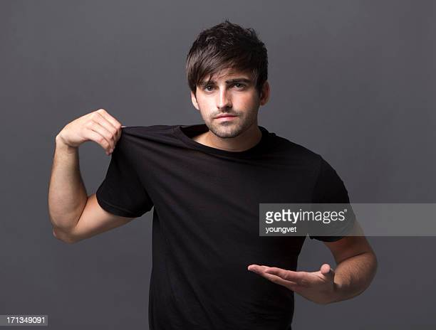 Handsome young man pointing at blank black shirt