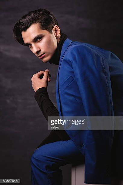 Handsome young man posing dressed in blue elegant suit