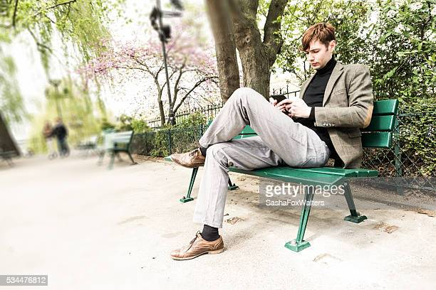 handsome young man reading on a park bench, Paris, France