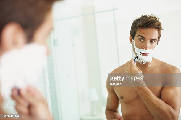 Handsome young man shaving off his beard