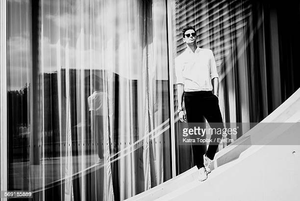 Handsome young man standing against glass window