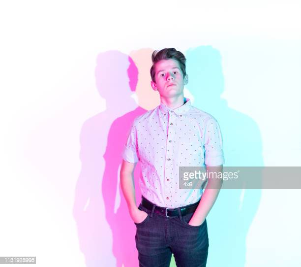 handsome young man standing against white wall with colorful shadows - gel effect lighting stock photos and pictures
