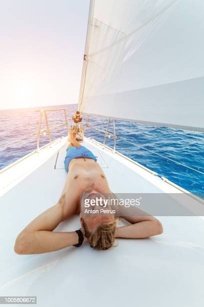 Handsome young man sunbathes on a white board yacht