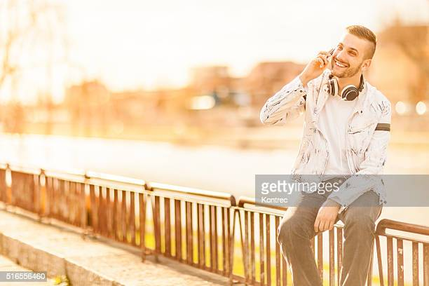 Handsome young man talking on the phone outdoors