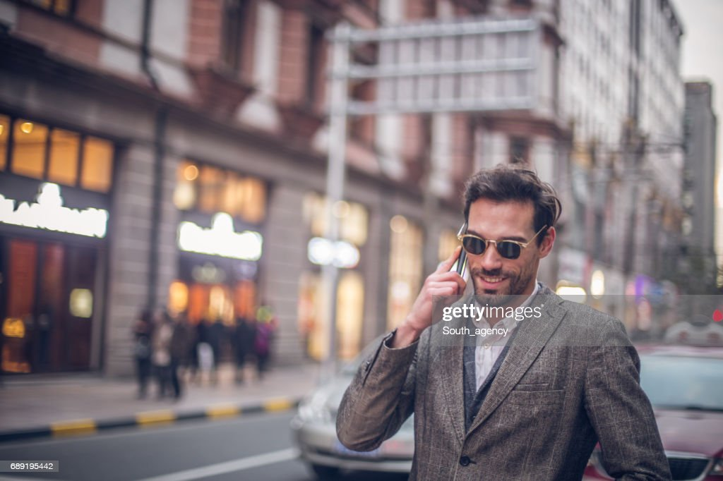 Handsome young man talking on the phone : Stock Photo