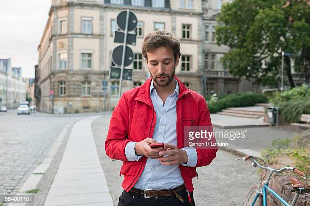 Handsome young man using cell phone in the city