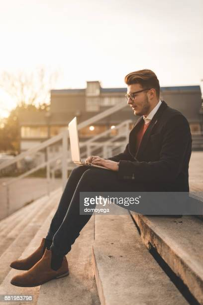 Handsome young man using laptop outdoors during autumn day