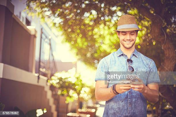 Handsome young man using smart phone outdoors on street