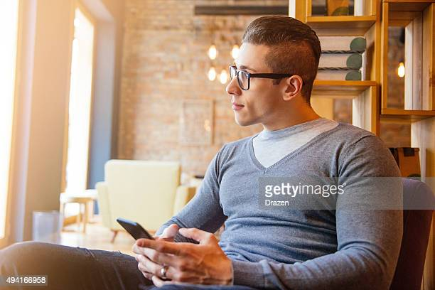 Handsome young man using smartphone for social networking and chat