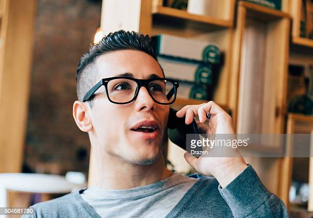 Handsome young man using smartphone for social networking and business
