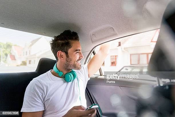 Handsome young man waving from car