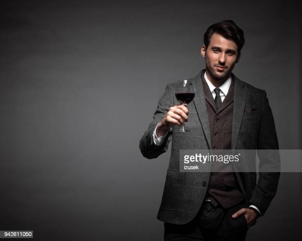 Handsome young man with a glass of wine