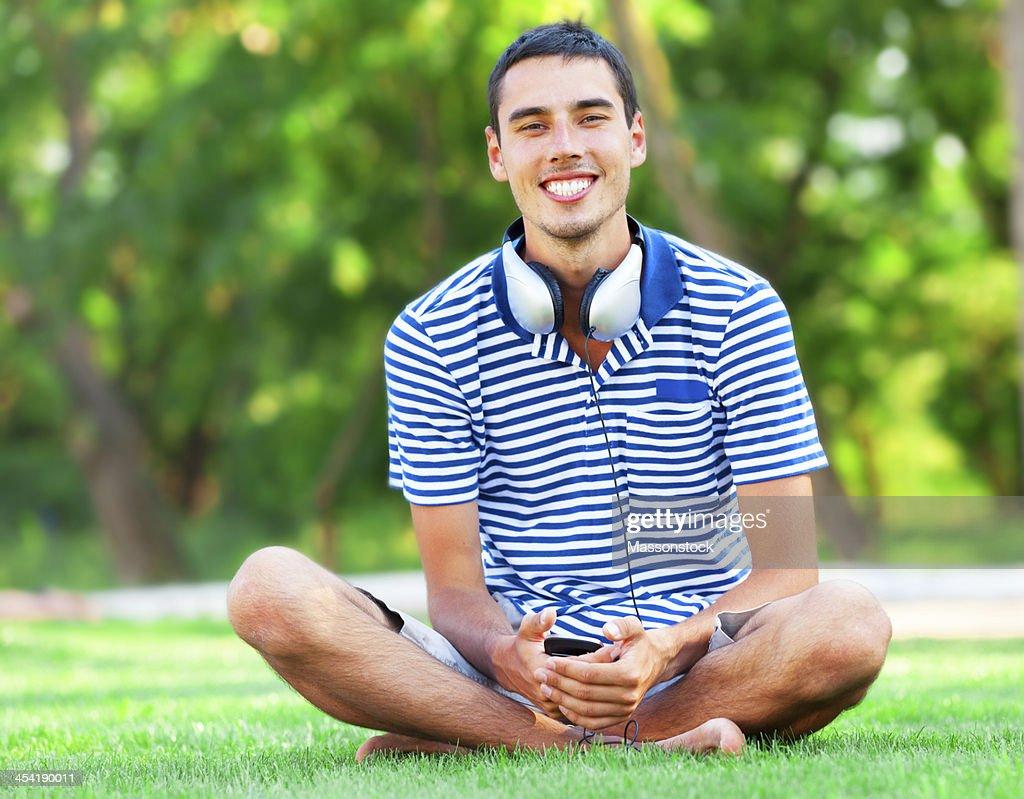 Gut aussehender junger Mann mit Kopfhörer auf grünem Gras : Stock-Foto