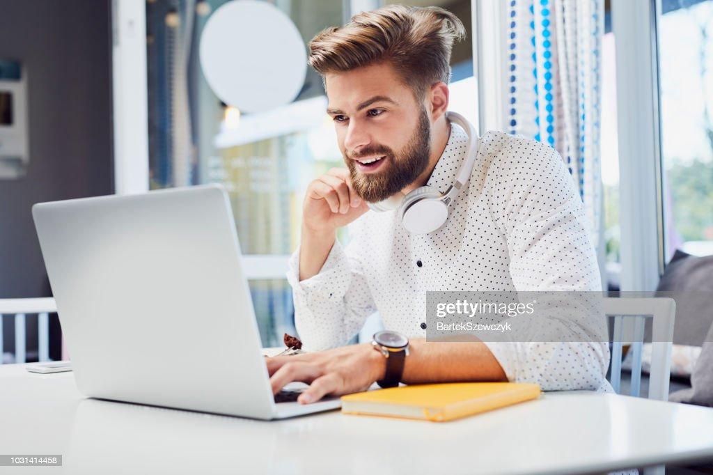 Hübscher junger Mann arbeiten am Laptop sitzen in modernen cafeteria : Stock-Foto