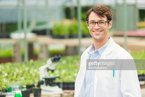 handsome young scientist at greenhouse laboratory - green glove stock photos and pictures