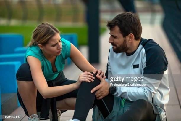 ハンサムな若いスポーツマンは、彼女の友人との練習中に膝の物理的な傷害を持っています - 靭帯 ストックフォトと画像