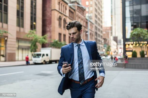 Handsone businessman in a hurry running through Manhattan, using smart phone