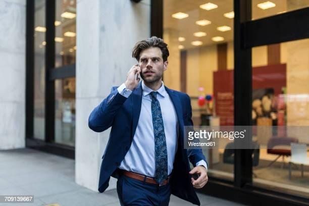Handsone businessman in a hurry running through Manhattan, using smart phone