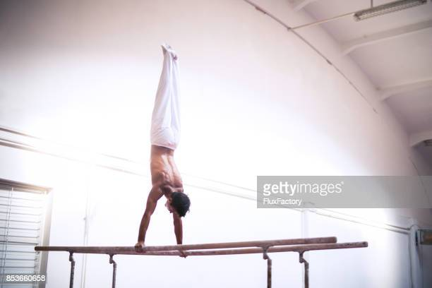 handstand on parallel bars - parallel bars gymnastics equipment stock photos and pictures