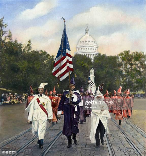Handtinted color photo shows the Ku Klux Klan in a parade in Washington DC