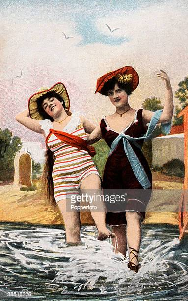 Hand-tinted studio photograph of two women in bathing costumes splashing in the sea, circa 1910.