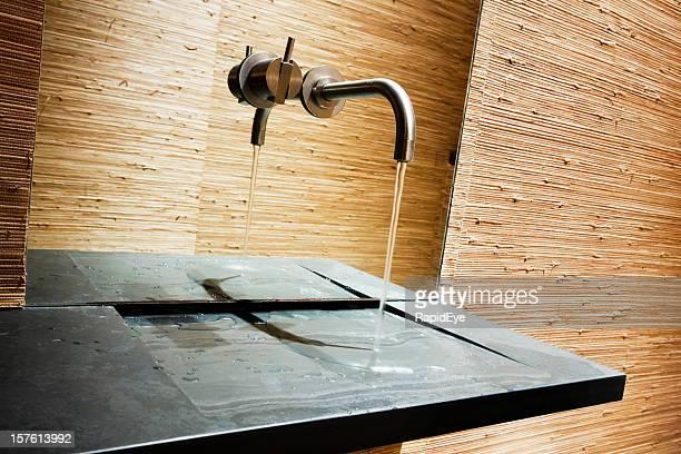 Handwashing water runs onto slate slab in ultramodern bathroom