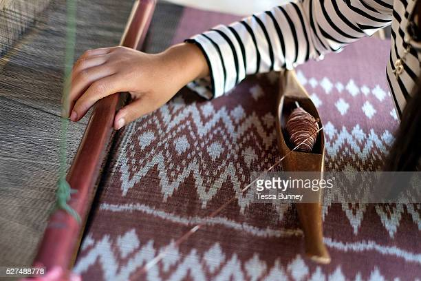 Handweaving organic cotton with a mutmee/tie dye design in Ban Lahanam, Savannakhet province, Lao PDR. In Savannakhet most textiles are dyed with...