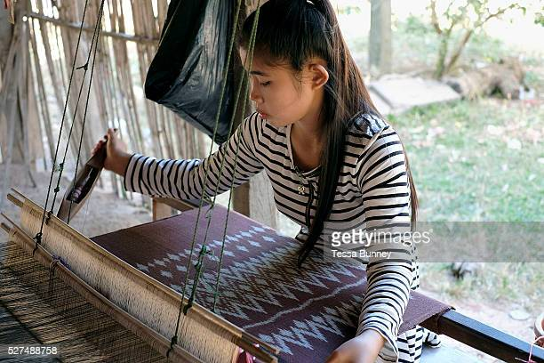 Handweaving organic cotton with a mutmee/tie dye design in the Phu Tai ethnic minority village of Ban Lahanam, Savannakhet province, Lao PDR. In...