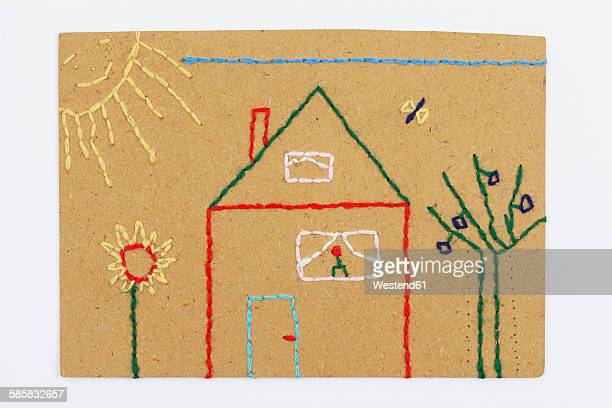 Handwork, embroidery, embroidered cardboard with wool, house with garden