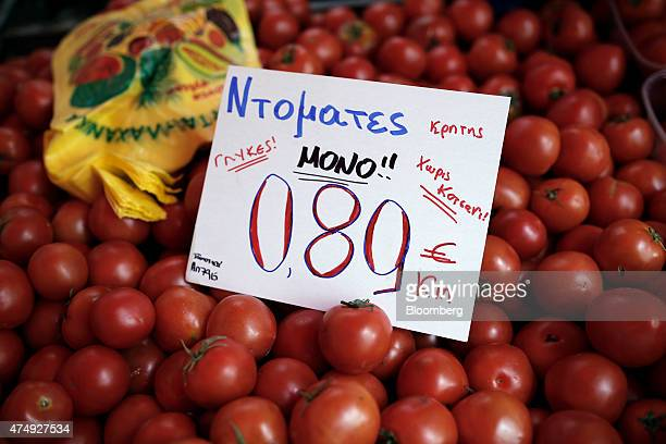 A handwritten euro sign indicates the per kilo euro price of fresh tomatoes for sale at a farmer's market on Kassandrou street in Thessaloniki Greece...