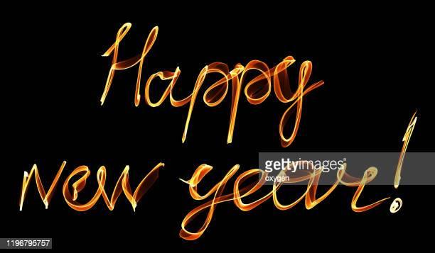 happy new year handwritten fire text brush - citation photos et images de collection