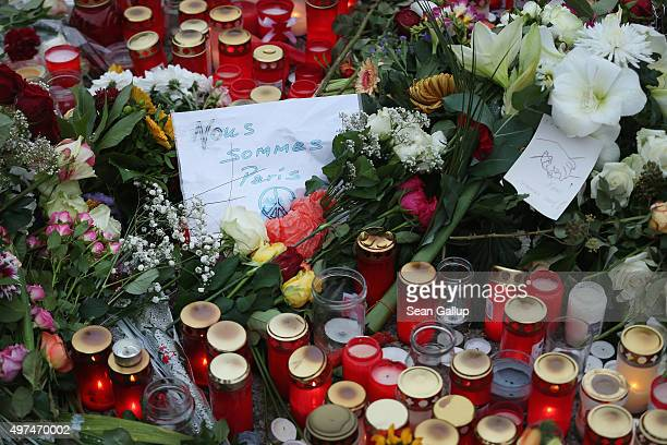 A handwritten message in French reads 'We are Paris' among candles messages and flowers left by mourners outside the French Embassy commemorating the...