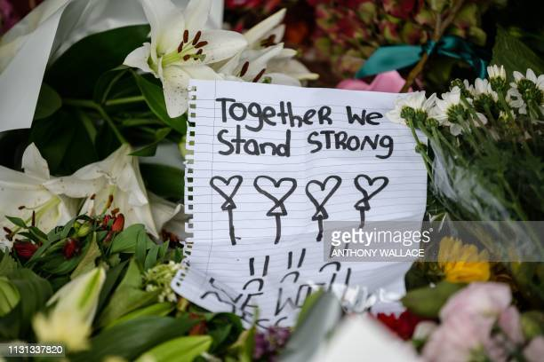 A handwritten note is displayed among flowers during a vigil in Christchurch on March 18 three days after a shooting incident at two mosques in the...