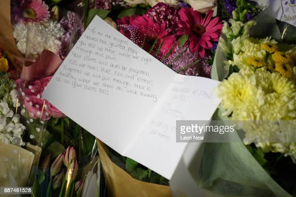A handwritten note is seen among floral tributes following an evening vigil outside the Town Hall on May 23 2017 in Manchester England An explosion...