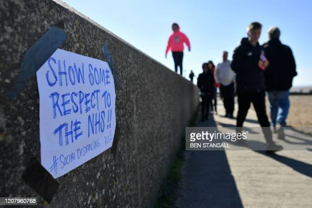 A handwritten notice asking people to Respect the NHS by practicing social distancing is seen on the seafront at Whitstable east of London on...