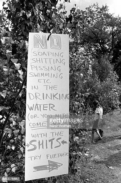 A handwritten rules poster hangs from a bush at Woodstock Music Art Fair celebrated in Bethel NY August 15 1969