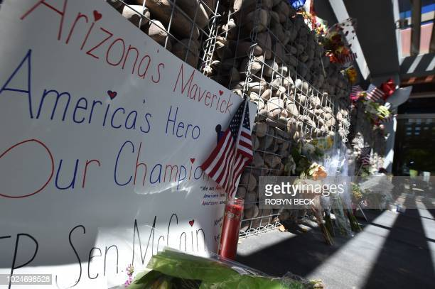 A handwritten sign and flowers are seen at a makeshift memorial remembering Senator John McCain outside McCain's office in Phoenix Arizona August 27...