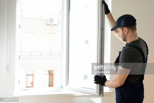 klusjesman die het venster bevestigt - raam stockfoto's en -beelden