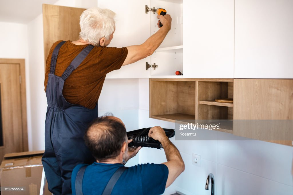 Handyman Holding A Tool Box While His Boss Installing A New Kitchen Cabinet High Res Stock Photo Getty Images